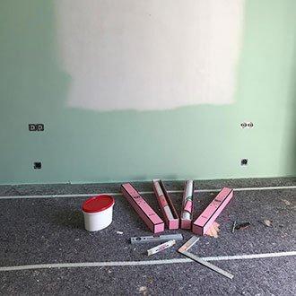 Utensilien zum Tapezieren liegen vor mintfarbener Wand