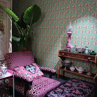 Pinker Sessel mit kleinen Mustern vor grüner Tapete mit kleinen Mustern
