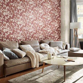 Eine rote Tapete mit beige geschlungenen Pflanzenornamenten in einem hell-beige eingerichtetem Wohnzimmer