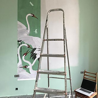 Erste Bahn der Kranichtapete ist an der Wand angebracht, davor steht eine Leiter