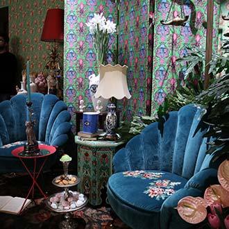 Blaue Sessel mit Blumen vor bunten Motivtapeten mit Blumen